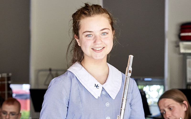 An image of a Merici Girl holding a flute in the music room