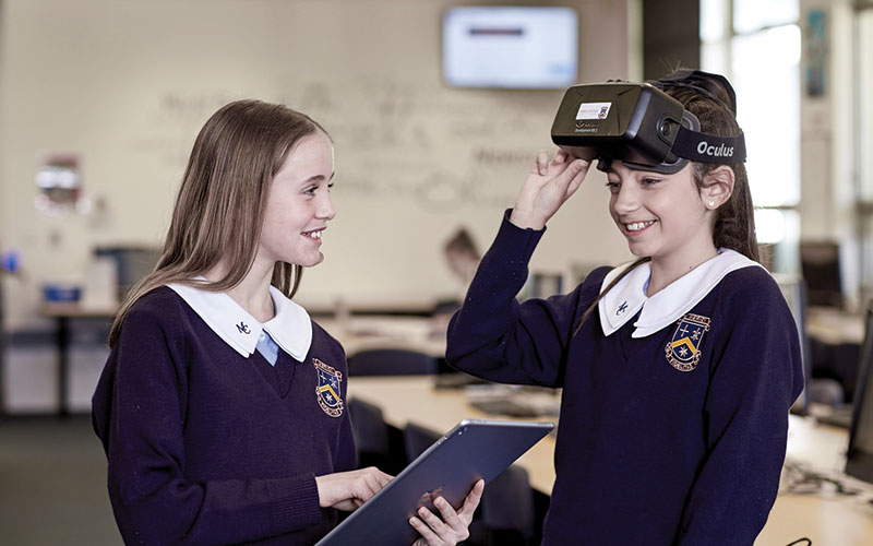 An image of Merici Junior students using an iPad and VR headset.
